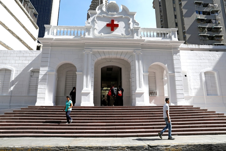 Image: People walk past a hospital run by the Venezuelan Red Cross in Caracas