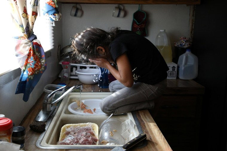 Image: Rachel, a migrant from Honduras, takes a break from washing a doll in the sink in Texico