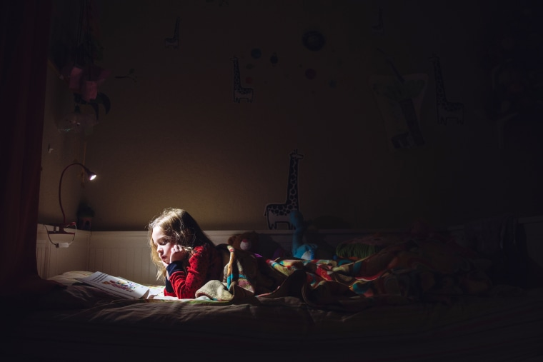 Image: A six year old girl is reading in her bed at night.