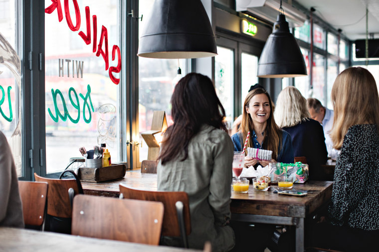 Smiling female friends enjoying while sitting at dining table for brunch in restaurant