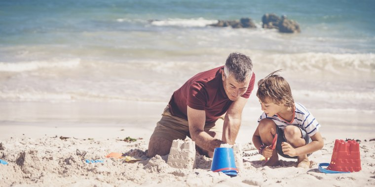 Father and boy making sandcastle on sunny day