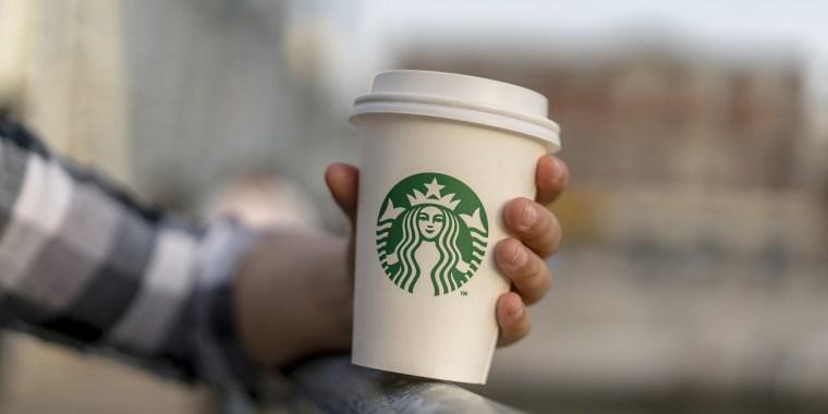 A girl holds a Starbucks coffee cup on a bridge.  Starbucks