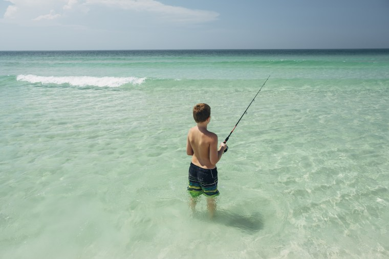 Rear view of shirtless boy fishing in sea