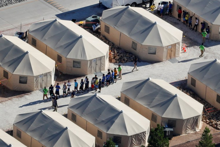 """Image: Immigrant children housed in a tent encampment under the new \""""zero tolerance\"""" policy by the Trump administration are shown walking in single file at the facility near the Mexican border in Tornillo, Texas"""