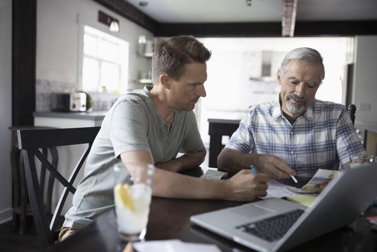 Image: Son helping senior father paying bills at laptop