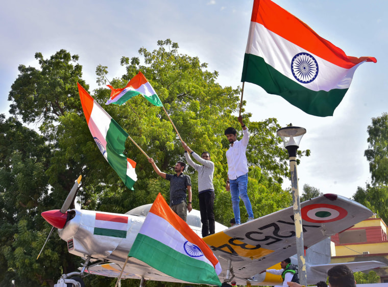 Image: Indian residents hold flags on a model of a military plane to celebrate the Indian Air Force (IAF) strike launched on a Jaish-e-Mohammad (JeM) camp at Balakot