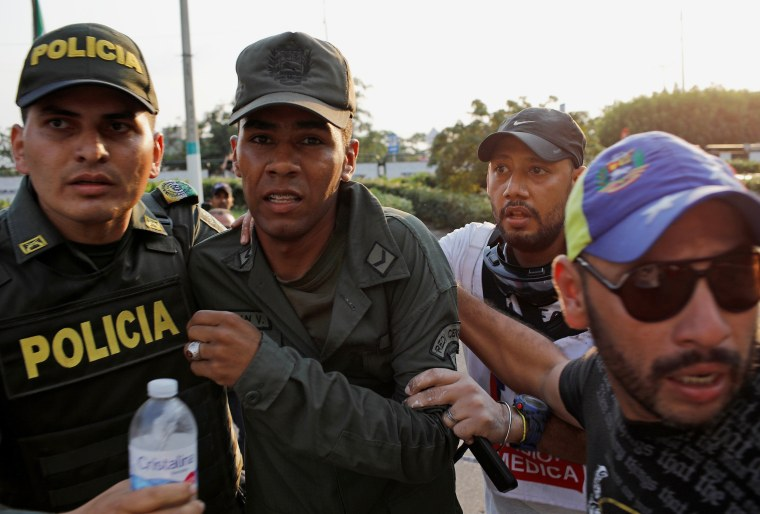 Image: A member of the Venezuelan National Guard who defected to Colombia is escorted by Colombian police in Cucuta on Feb. 25, 2019.