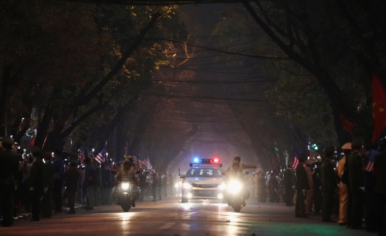 Image: Bystanders line the road as the motorcade of U.S. President Donald Trump approaches in Hanoi