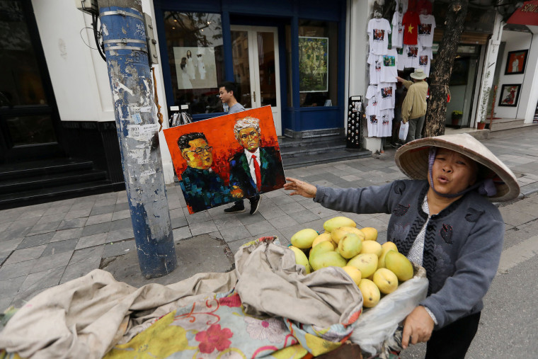 Image: A man walks past a vendor while holding a painting of North Korean leader Kim Jong Un and U.S. President Donald Trump ahead of the North Korea-U.S. summit in Hanoi
