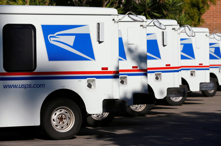 Image: U.S. postal service trucks sit parked at the post office in Del Mar, California