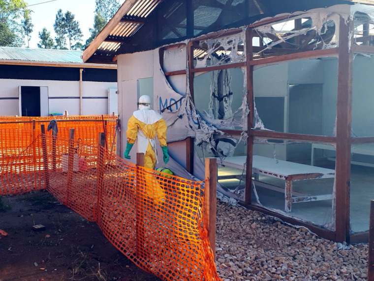 Image: A health worker dressed in a protective suit walks past burned structures after attackers set fire to an Ebola treatment center run by Medecins Sans Frontieres (MSF) in the east Congolese town of Katwa