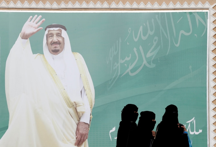 Image: FILE PHOTO: Women walk past a poster of Saudi Arabia's King Salman bin Abdulaziz Al Saud during Janadriyah Cultural Festival on the outskirts of Riyadh