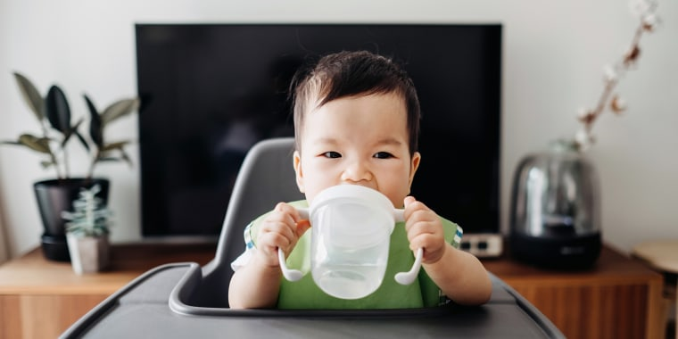 Cute baby drinking water from sip cup on high chair
