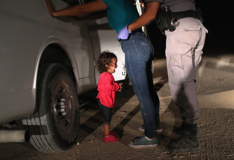 Image: A two-year-old Honduran asylum seeker cries as her mother is searched and detained near the U.S.-Mexico border