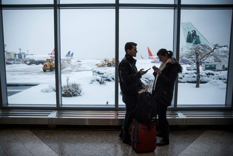 Image: Travelers check their phones while waiting for a flight at LaGuardia Airport during a winter storm in Queens, New York, on Feb. 2, 2015.