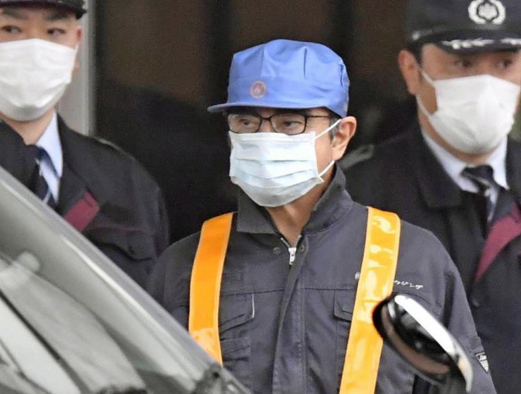 Image: A masked man, believed to be former Nissan Chairman Carlos Ghosn, leaves Tokyo's Detention Center