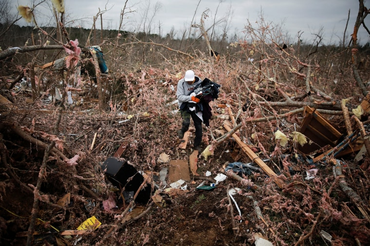 Image: Dax Leandro salvages clothing from the wreckage of his friend's home after two back-to-back tornadoes touched down, in Beauregard