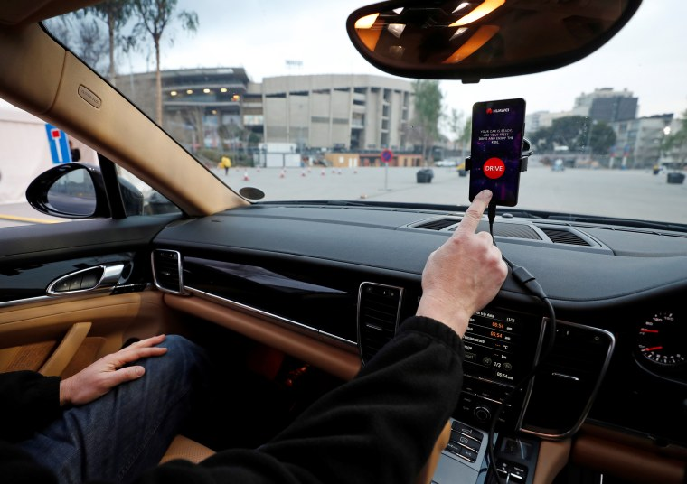 An engineer points to a Huawei Mate 10 Pro mobile used to control a driverless car during the Mobile World Congress in Barcelona