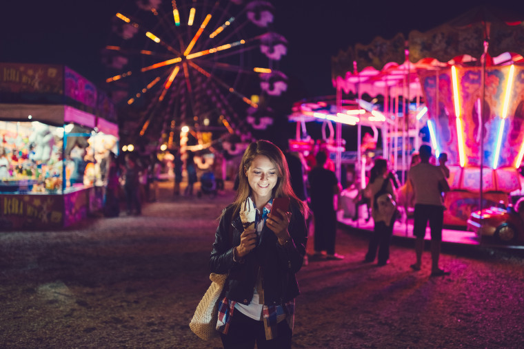 Image: Smiling woman texting at the amusement park