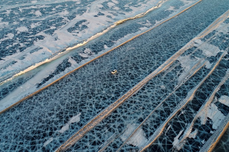 Image: A car drives along a road connecting the banks of the ice-covered Yenisei River south of Krasnoyarsk