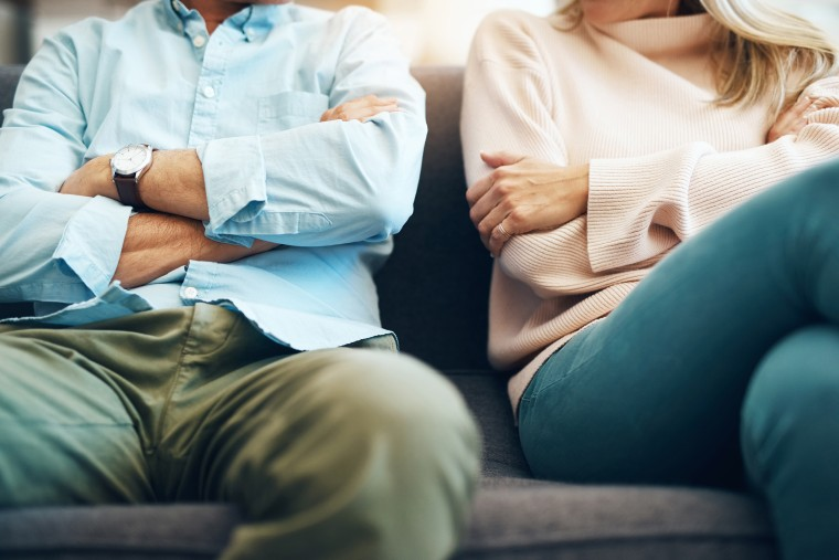 Image: mature couple sitting on the sofa with their arms folded after an argument