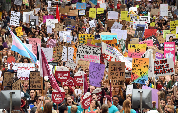 Image: People hold up banners as thousands march to mark International Women's Day in Melbourne