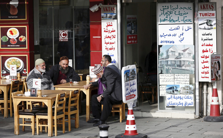 Image: Men chat in front of a real estate agency in Istanbul which has Arabic notices on its window