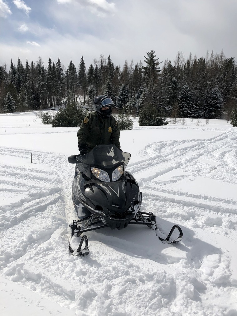 An Agent with U.S. Customs and Border Protect patrols the line between Vermont and Quebec on his snowmobile.