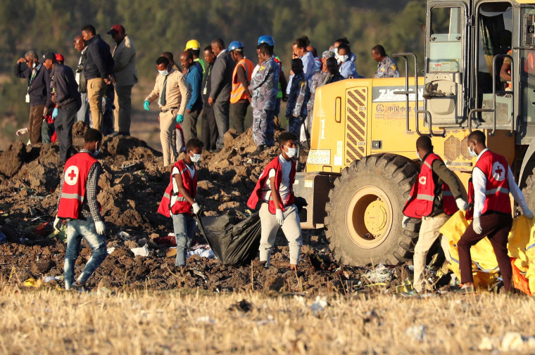 Image: Members of the search and rescue mission carry dead bodies at the scene of the Ethiopian Airlines Flight ET 302 plane crash, near the town of Bishoftu