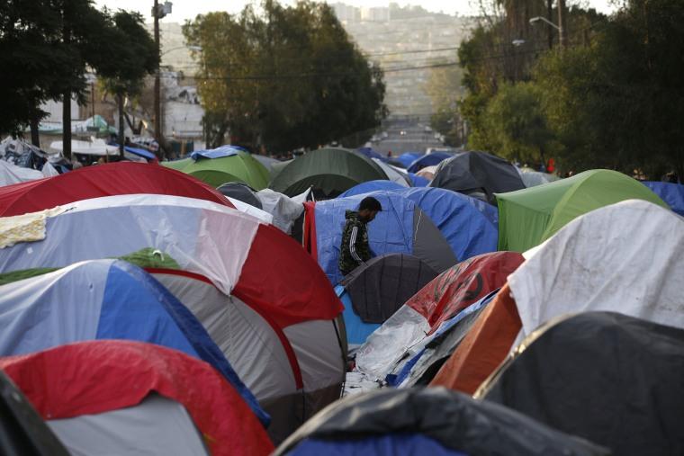 Image: A migrant walks into a migrant tent camp outside the closed Benito Juarez sports complex in Tijuana, Mexico