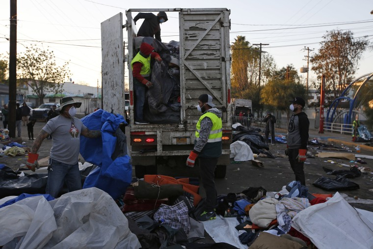 Image: Workers clean a street where authorities evicted a group of Central Americans who had remained camped outside the closed Benito Juarez sports complex, in Tijuana, Mexico
