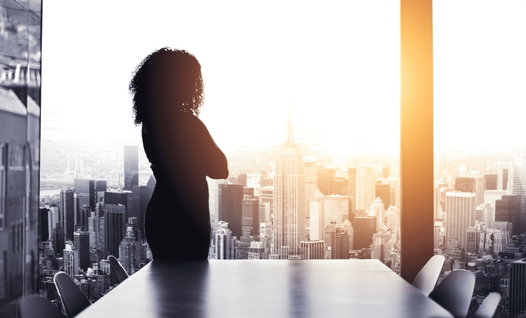 Image: Silhouetted shot of a young businesswoman looking at a cityscape from an office window