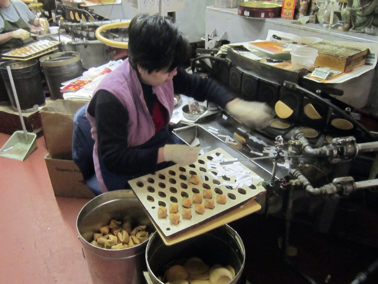 A woman folds and inserts fortunes into cooling cookies at the Golden Gate Fortune Cookie Company, in San Francisco's Chinatown in 2013.