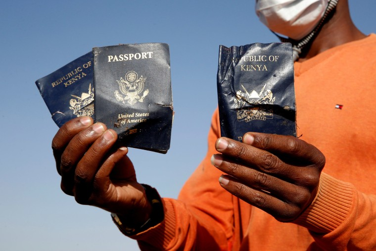 Image: Man holds passengers' passports found at the scene of the Ethiopian Airlines Flight ET 302 plane crash, near the town of Bishoftu, near Addis Ababa