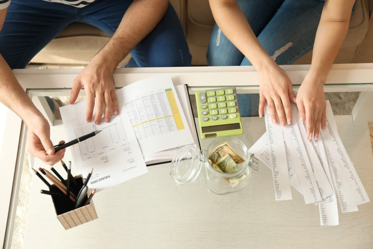 Image: Couple with pay bills, calculator and money counting expenses indoors. Money savings concept