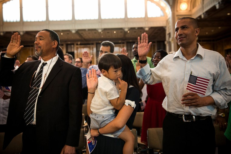 Image: Miyoung Lee holds her son, Nate, as they take part in a United States naturalization ceremony at the New York Public Library on July 2, 2014.