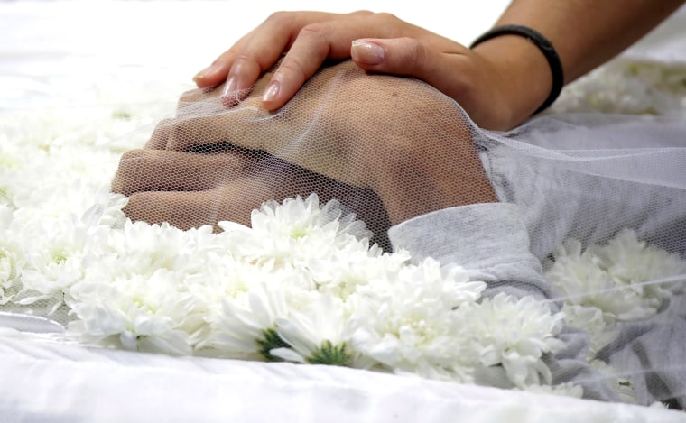 Image: A mourner touches the hand of one of the victims killed in a shooting at Raul Brasil School, during the collective funeral in Suzano