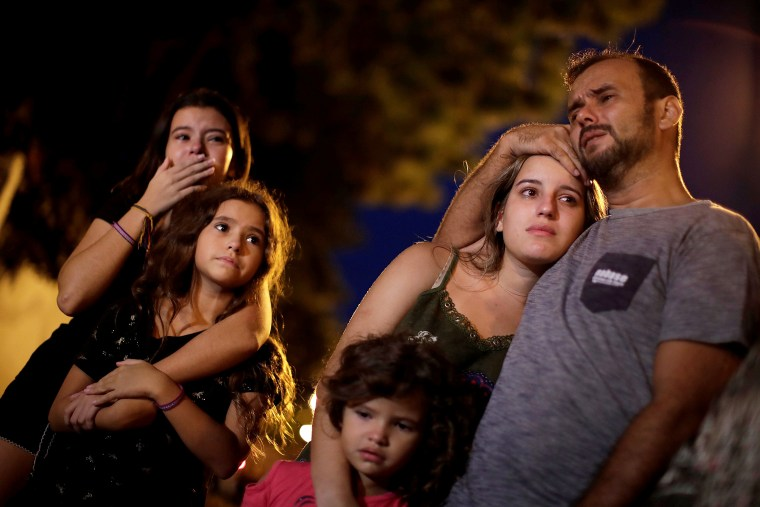 Image: Relatives, friends and students react as they pay tribute to victims of the shooting in Raul Brasil school in Suzano