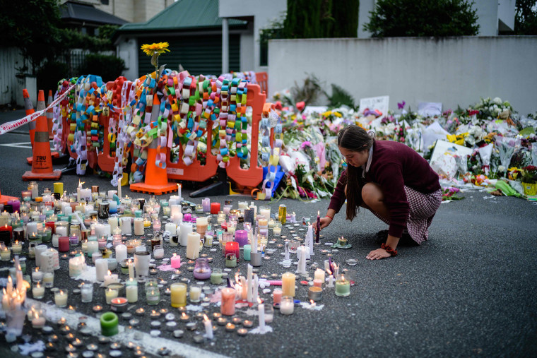 Image: A student places a candle next to flower tributes for the victims after a vigil in Christchurch
