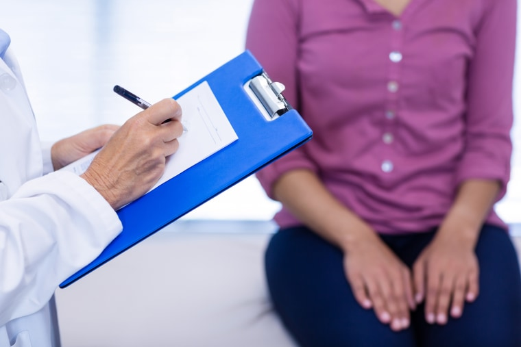 Doctor writing on clipboard in clinic