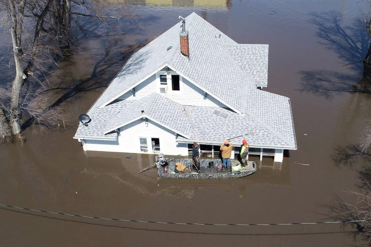 Image: Lanni Bailey and a team from Muddy Paws Second Chance Rescue enter a flooded house to pull out several cats during flooding of the Missouri River near Glenwood