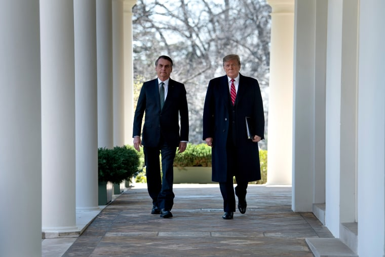 Image: Brazil's President Jair Bolsonaro and President Donald Trump walk to a press conference in the Rose Garden on March 19, 2019.