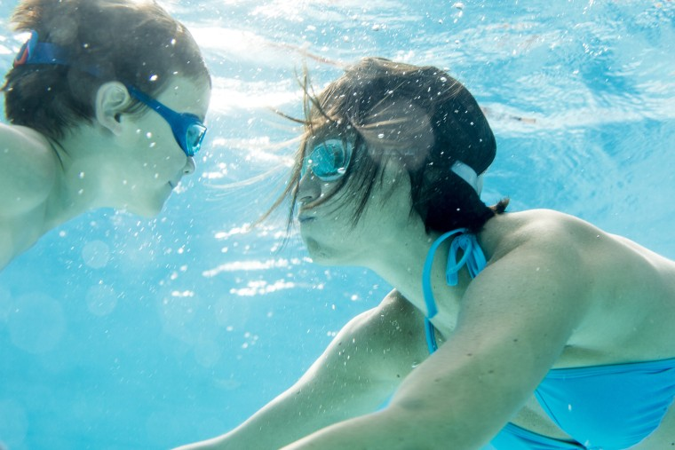 Image: Boy diving underwater with his mum, swimming pool