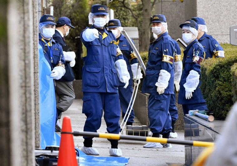 Image: Police investigate the scene after a woman was stabbed by her husband at a court in Tokyo on March 20, 2019.