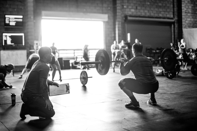 Trainer observing cross training athlete doing squats with barbell in gym