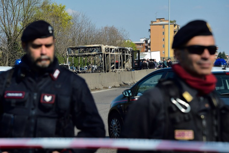 Image: Italian Carabinieri policemen stand by by the wreckage of a school bus that was transporting some 50 children