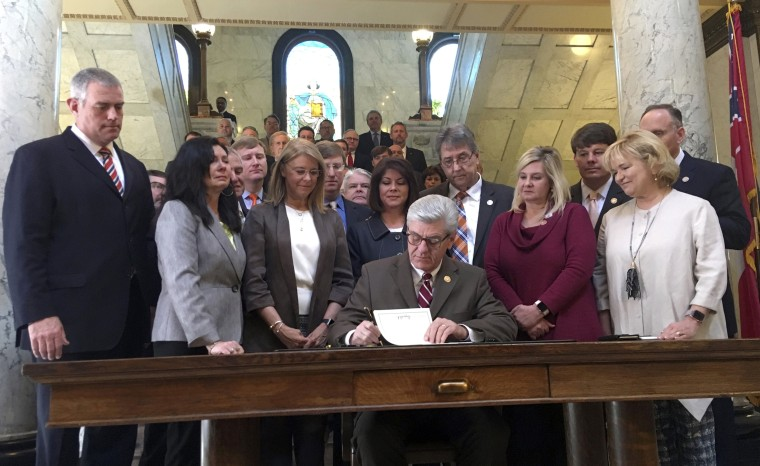 Image: Mississippi Governor Phil Bryant signs a bill that will ban most abortions once a fetal heartbeat is detected in Jackson on March 21, 2019.