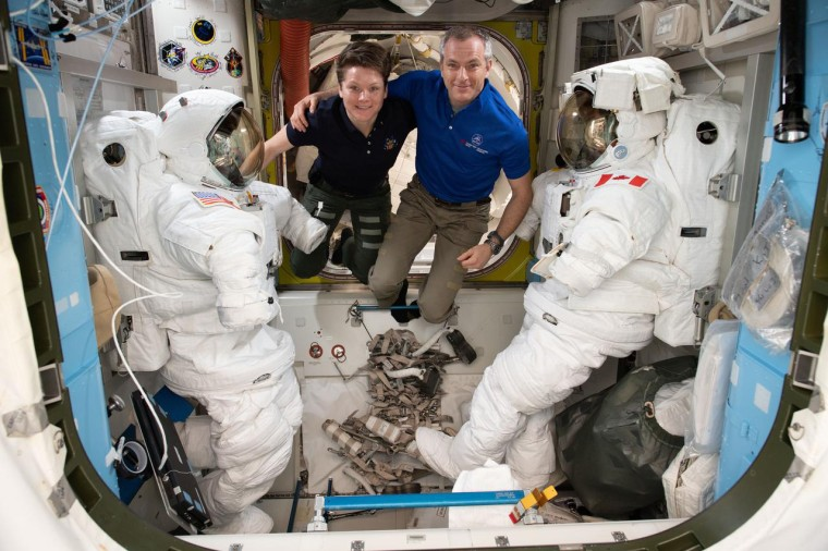Image: Astronauts Anne McClain and David Saint-Jacques are pictured in between a pair of spacesuits that are stowed and serviced inside the Quest airlock where U.S. spacewalks are staged.