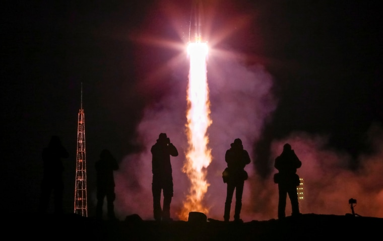 Image: Photographers take pictures as the Soyuz MS-12 spacecraft carring the next International Space Station (ISS) crew blasts off from the launchpad at the Baikonur Cosmodrome