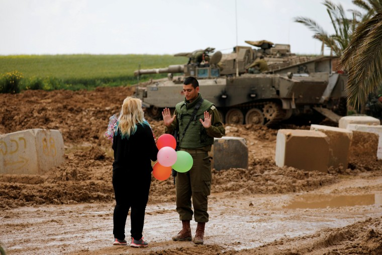 Image: A woman gives balloons to an Israeli soldier near the border between Israel and Gaza on its Israeli side